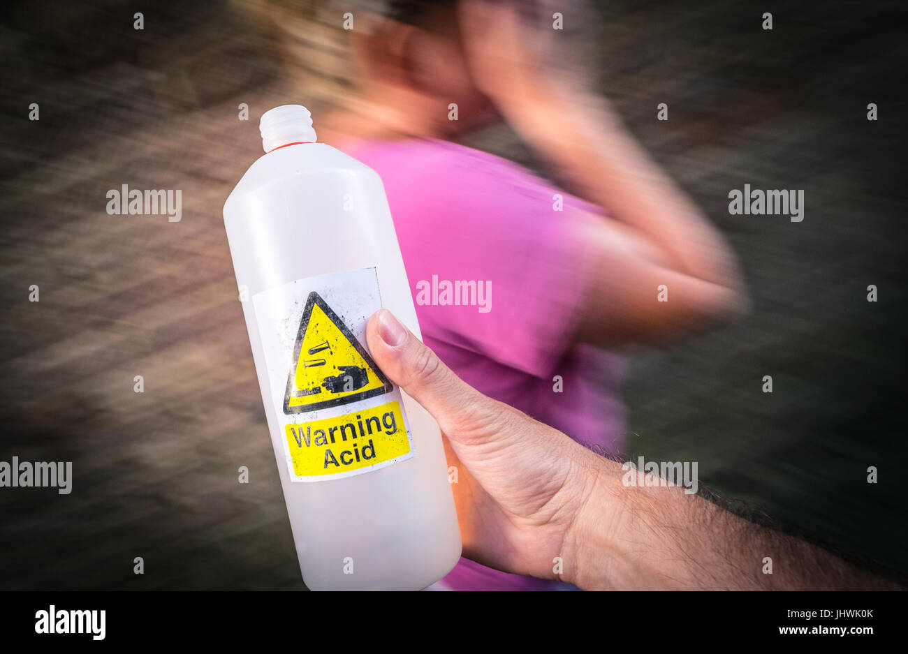 Acid Attack, A man holding an acid bottle in the street near a passing woman - Stock Image