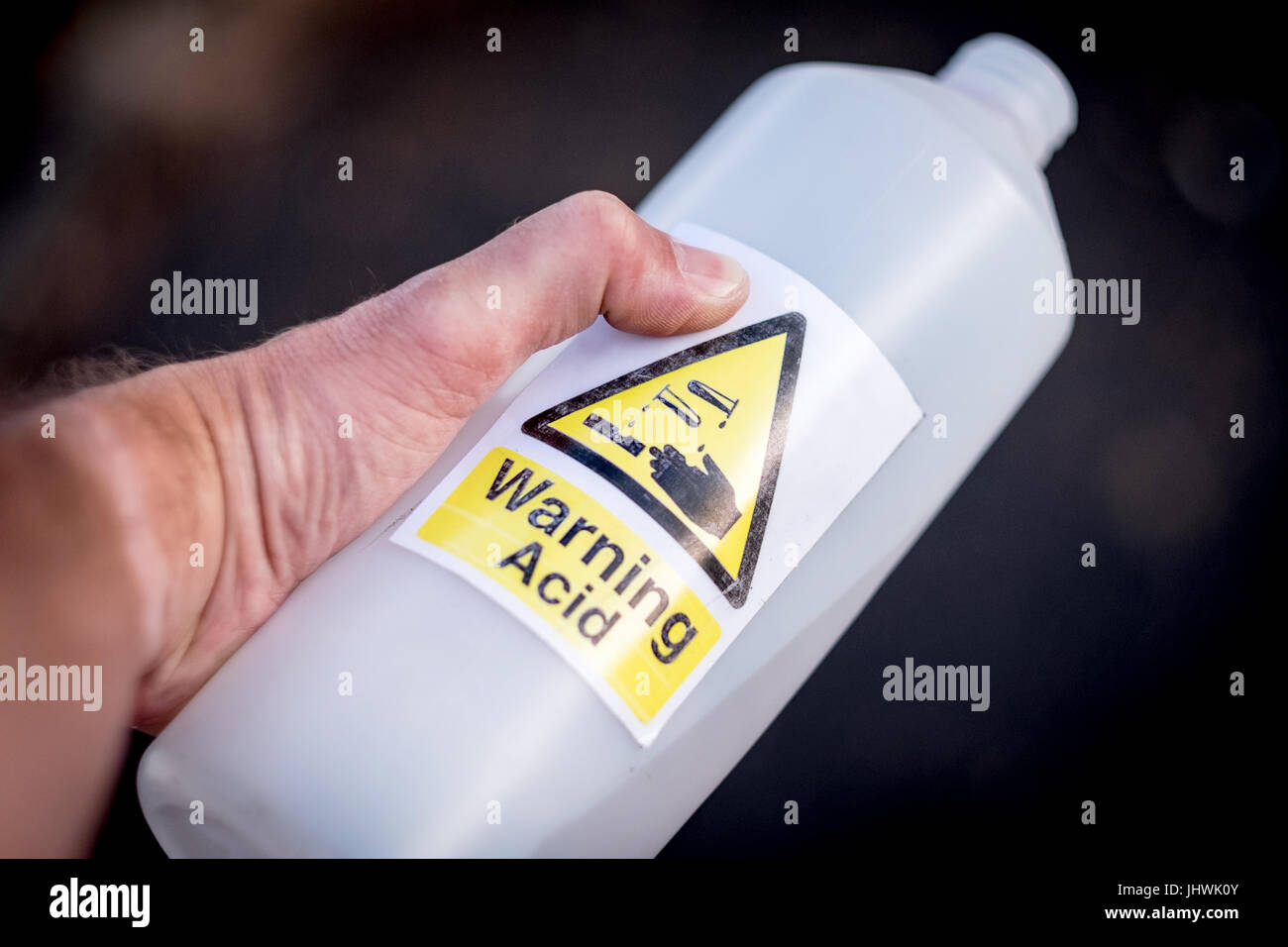 Acid Attack, A man holding an acid bottle in the street - Stock Image