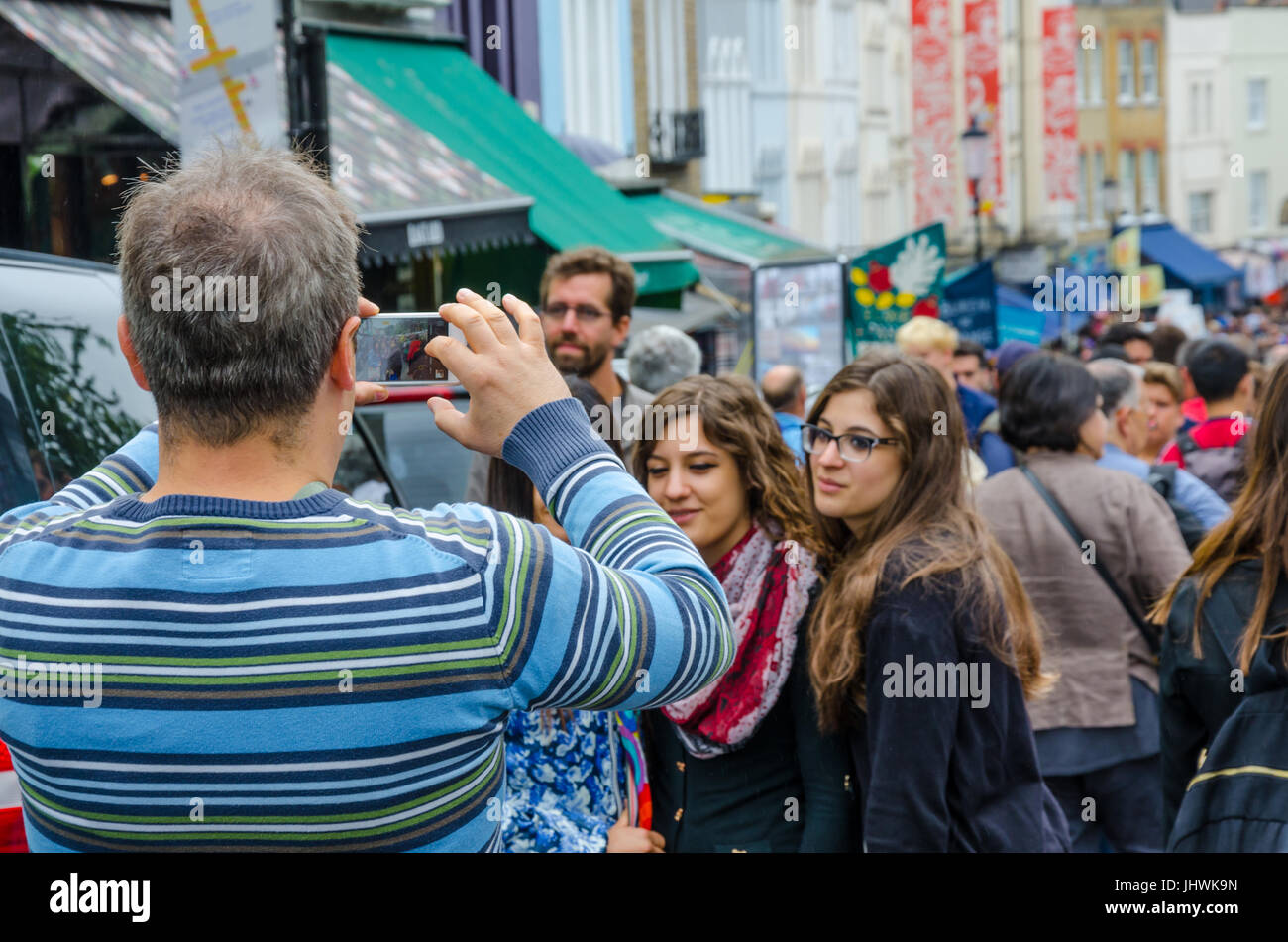 A family pose for a selfie taken on a mobile phone on Portobello Road in Notting Hill, London. - Stock Image