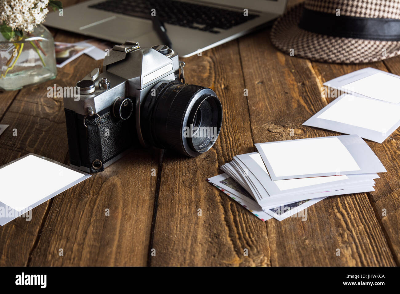 Vintage photo camera. Blank photo frames. Old photographs of paper, on wooden background, next to modern computer Stock Photo