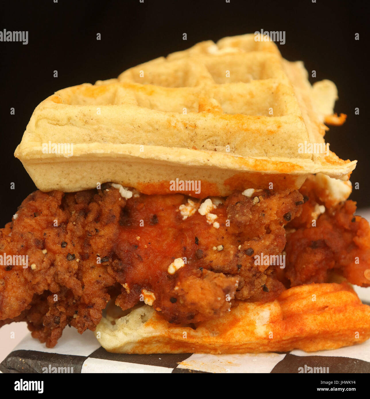 Belgian waffle sandwich with hot battered chicken, feta cheese, hot sauce and spices - Stock Image