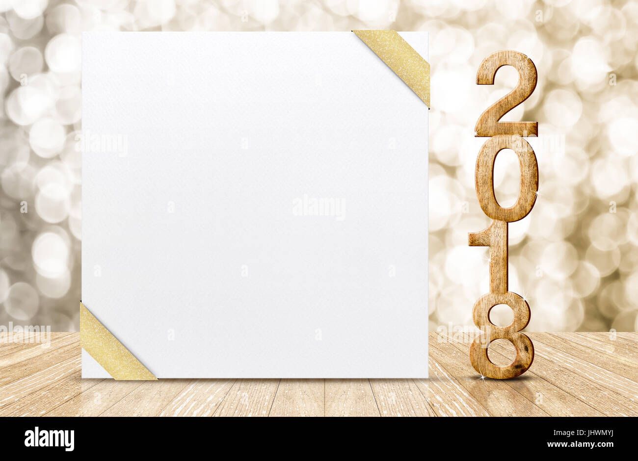 happy new year 2018 with blank white greeting card with gold ribbon in perspective room at sparkling bokeh wall and wooden plank floorleave space for