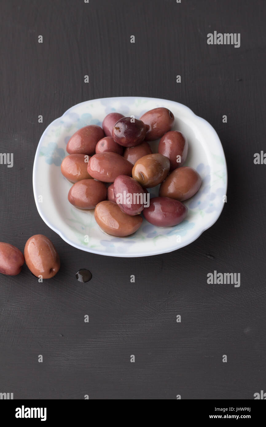 Purple olives in small white bowl with two on black chalk board texture background - vertical daylight shot with - Stock Image