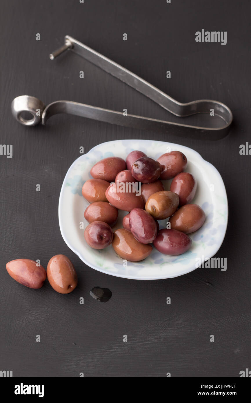 Purple olives in small white bowl with two on black chalk board texture background with olive pitter - vertical - Stock Image