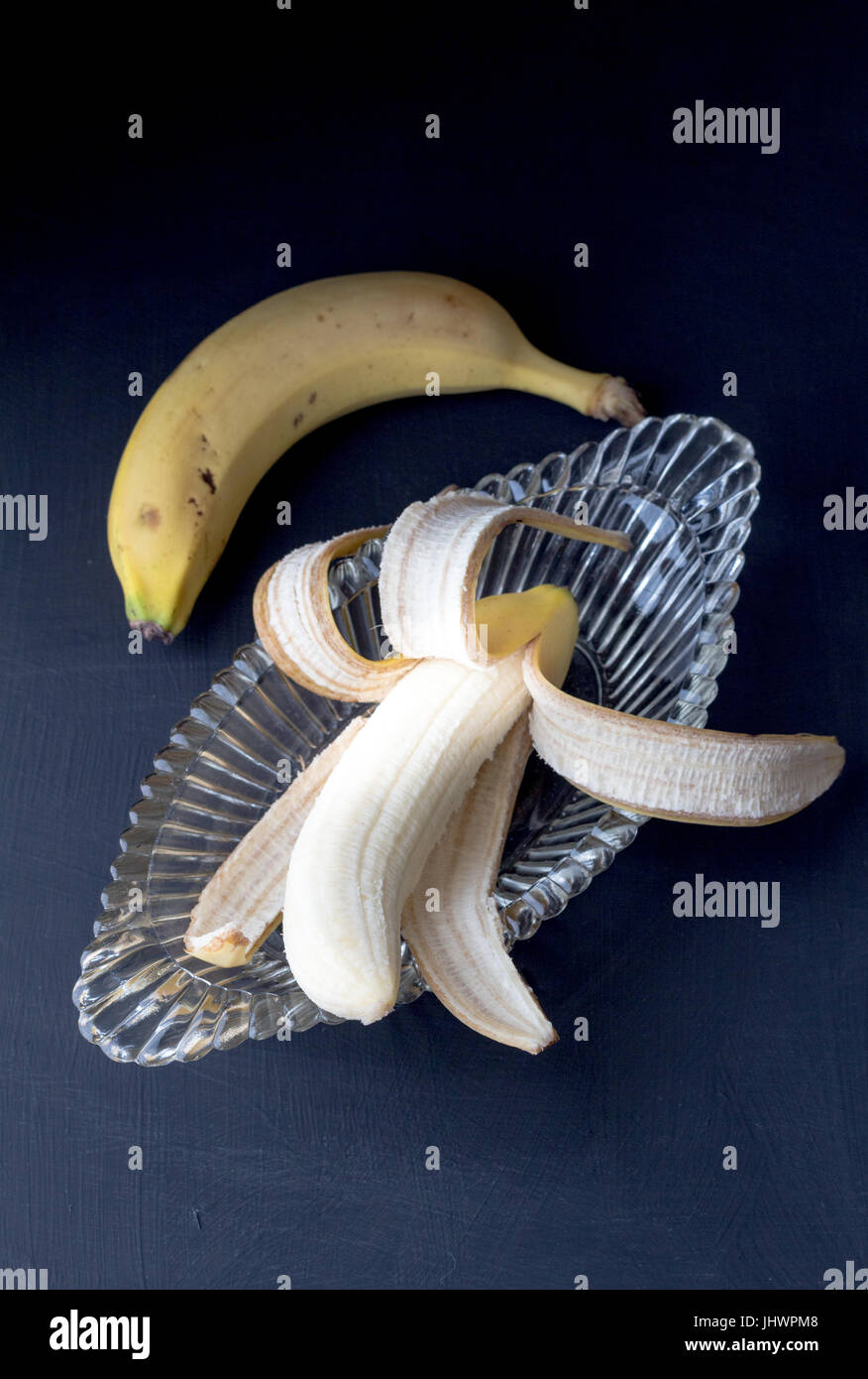 Banana peeled in glass banana split antique bowl with selective focus and one unpeeled on black background - daylight - Stock Image