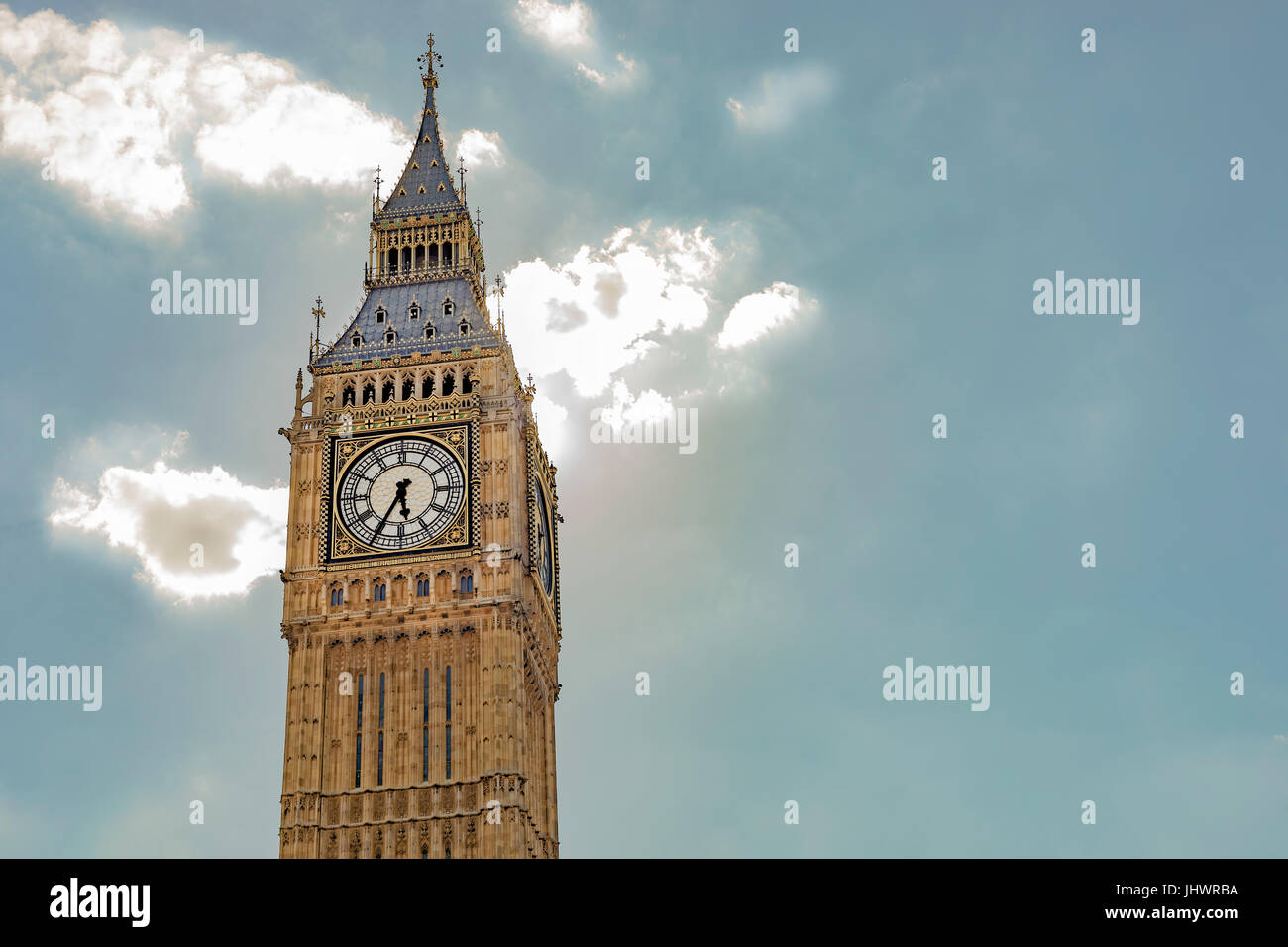 Elizabeth Tower with the clock and the bells of Big Ben in front of a bright blue sky with luminous clouds. - Stock Image