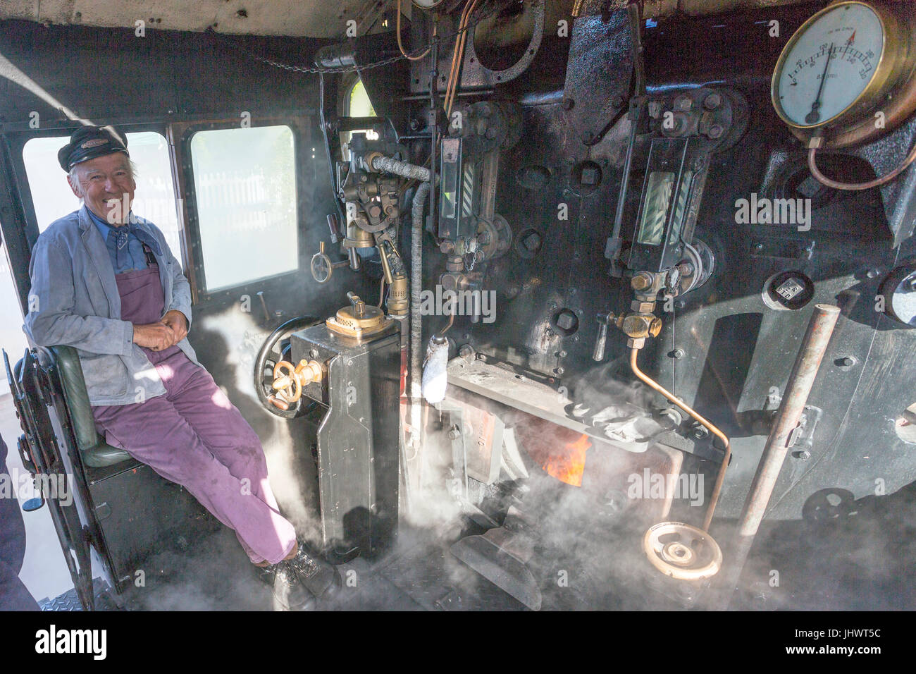 The driver on the steamy footplate of  Ex-BR loco 78018 waiting to take his train to Minehead on the West Somerset Stock Photo
