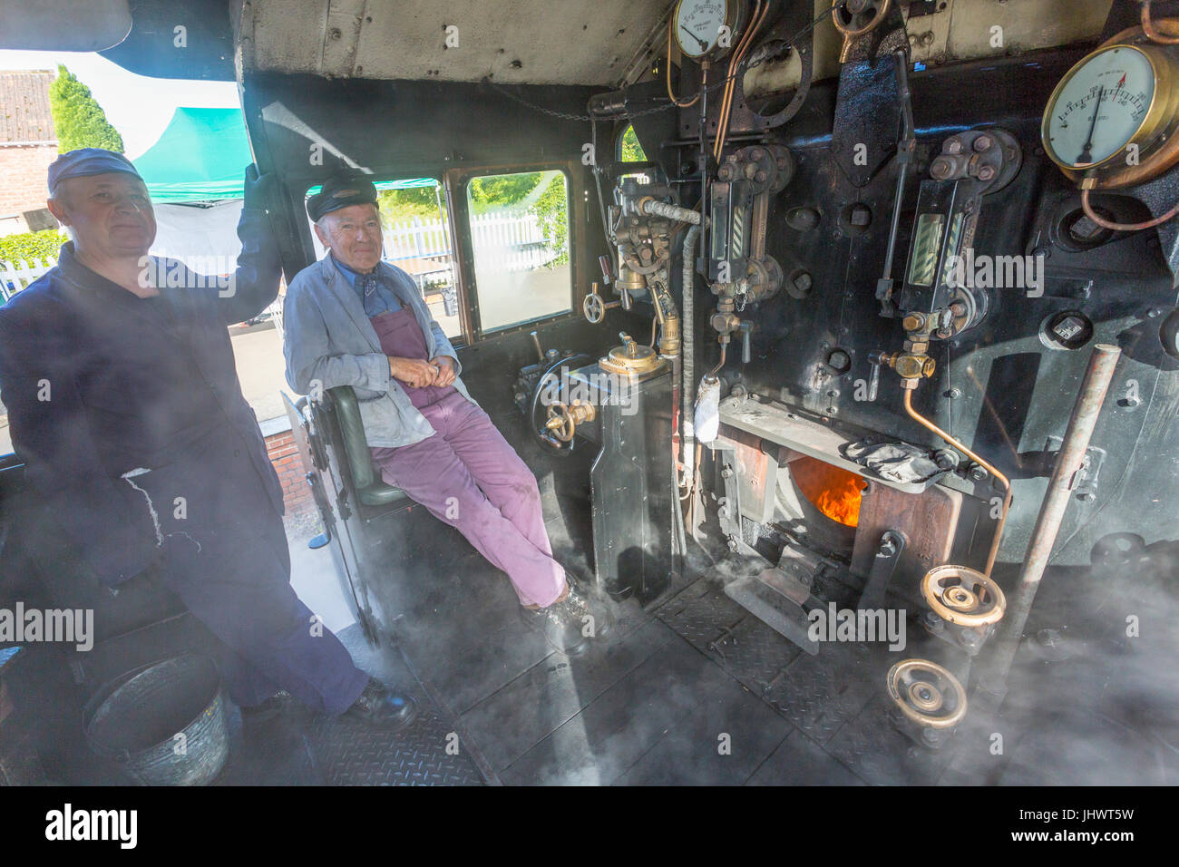 The driver and fireman on the steamy footplate of  Ex-BR loco 78018 waiting to take their train to Minehead on the Stock Photo
