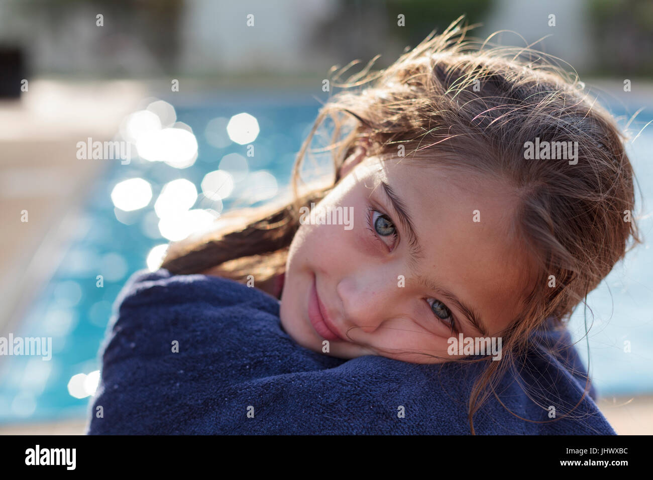 Young girl wrapped in blue towel after swimming in pool Stock Photo