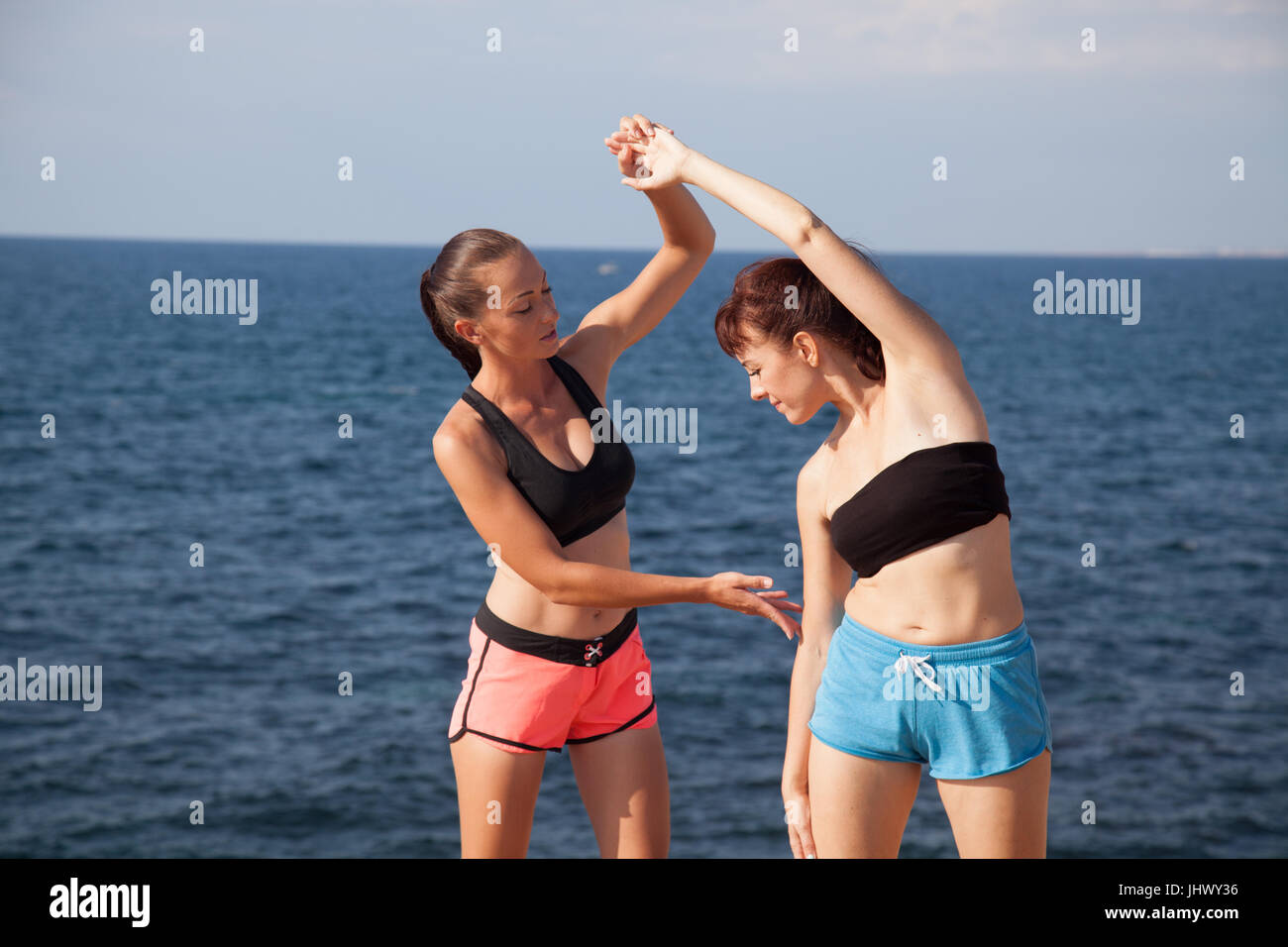 fitness trainer shows woman sport exercises - Stock Image