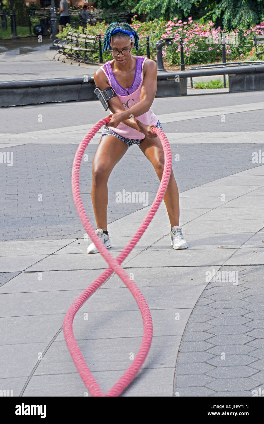 An attractive fit muscular young lady working out on the battle ropes during an outdoor fitness class in Washington - Stock Image