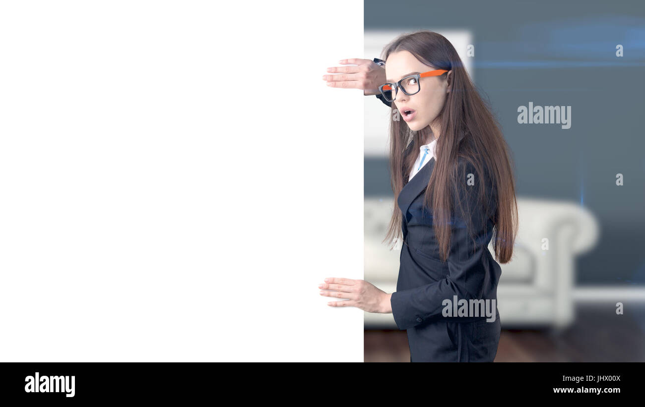 Young beautiful business woman and creative designer standing over blured interior background - Stock Image