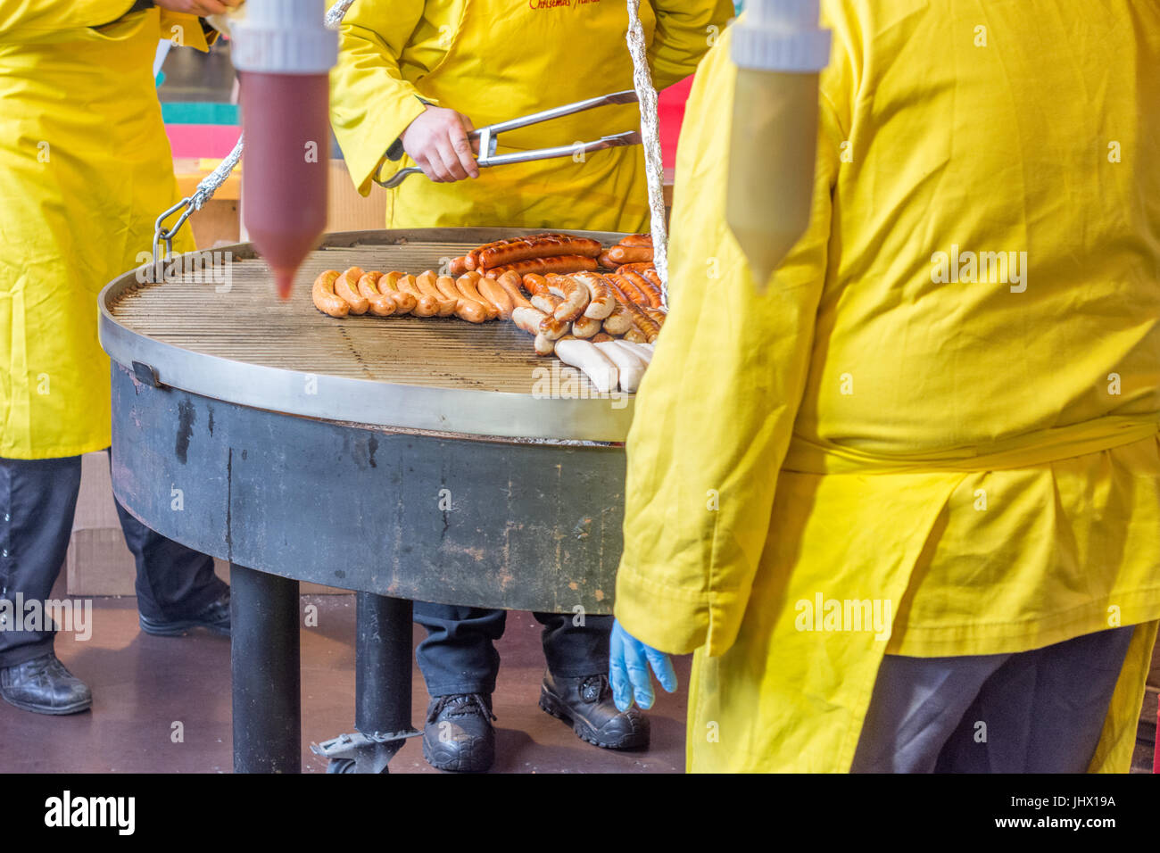 Grilling typical German Market sausages in a market stall. Stock Photo