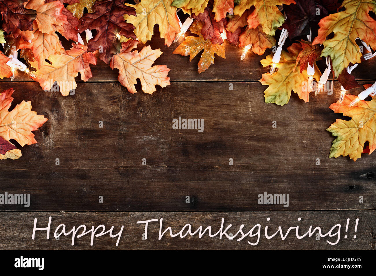 Rustic Fall Background Of Autumn Leaves And Decorative Lights With Happy Thanksgiving Text Over A Barn Wood Image Shot From