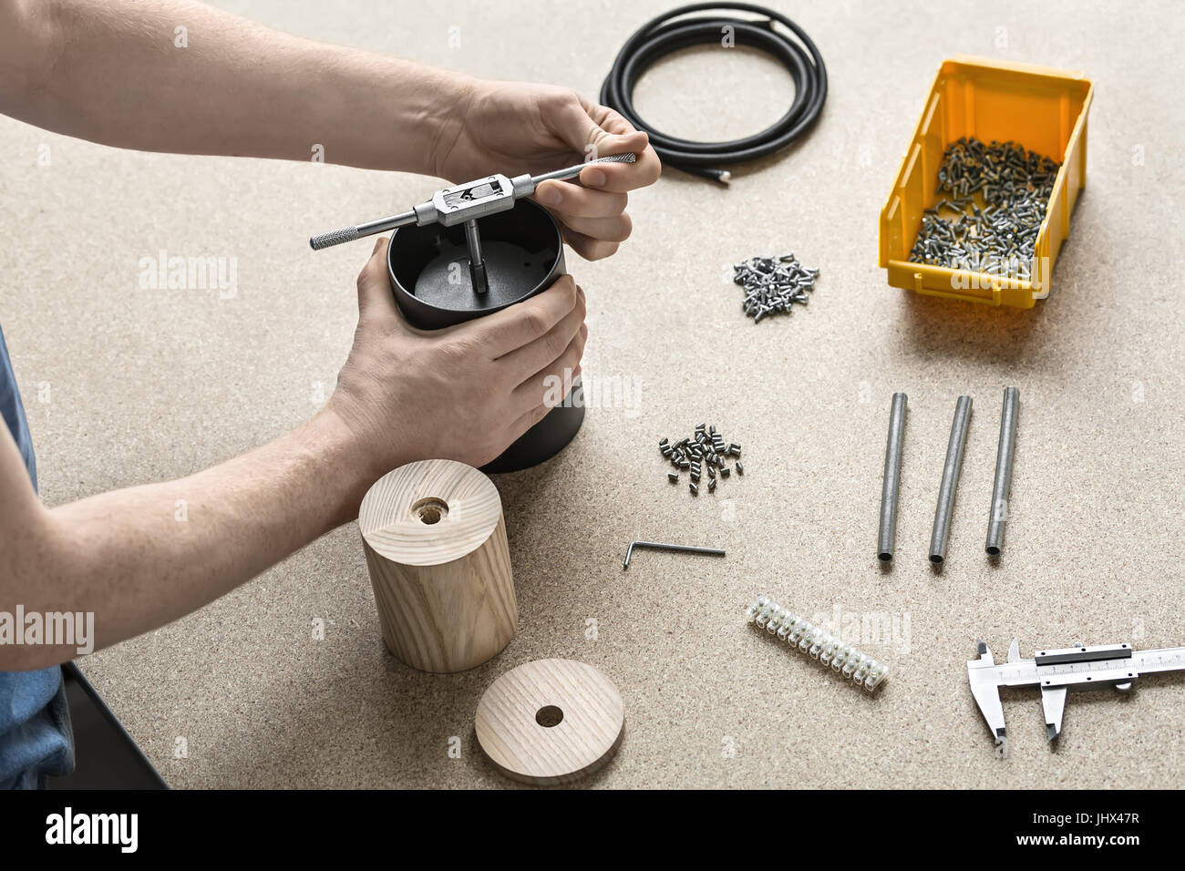 Man with tattoo is using a t-wrench on a black metal cylinder on the light table. On the table there are wooden - Stock Image