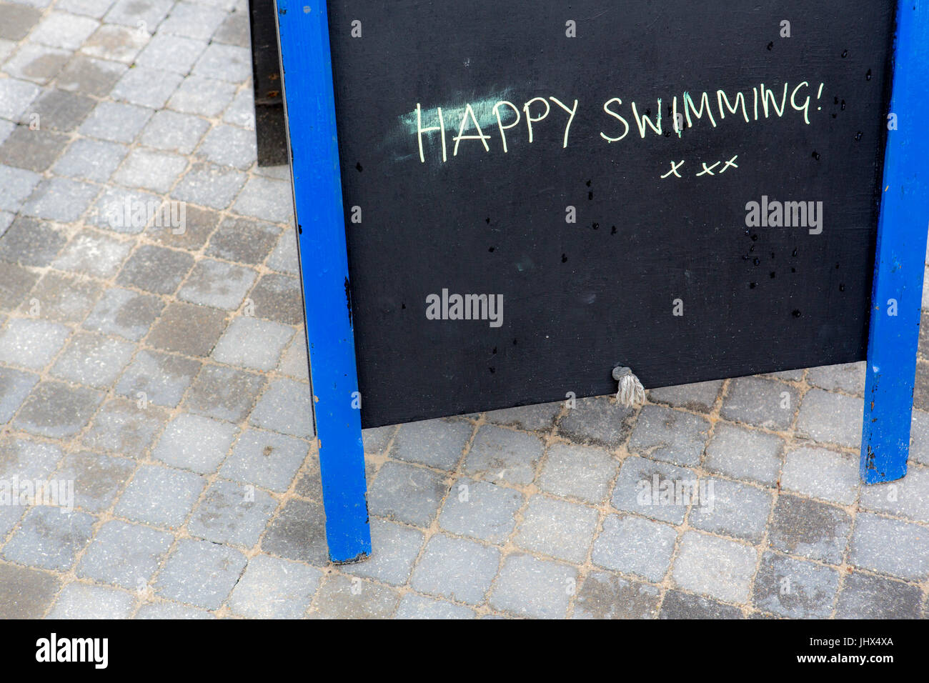 A small hand written sign on a blackboard at a lcoal town swimming pool wishing people a happy swim. - Stock Image