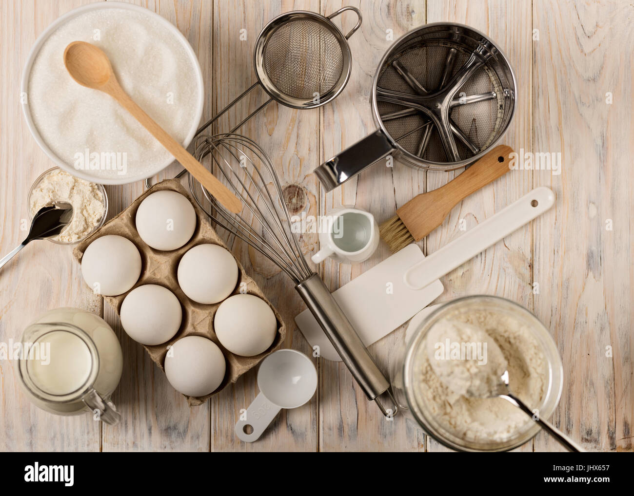Kitchen utensils and tools for homemade baking on a light wooden background. Selective focus. - Stock Image