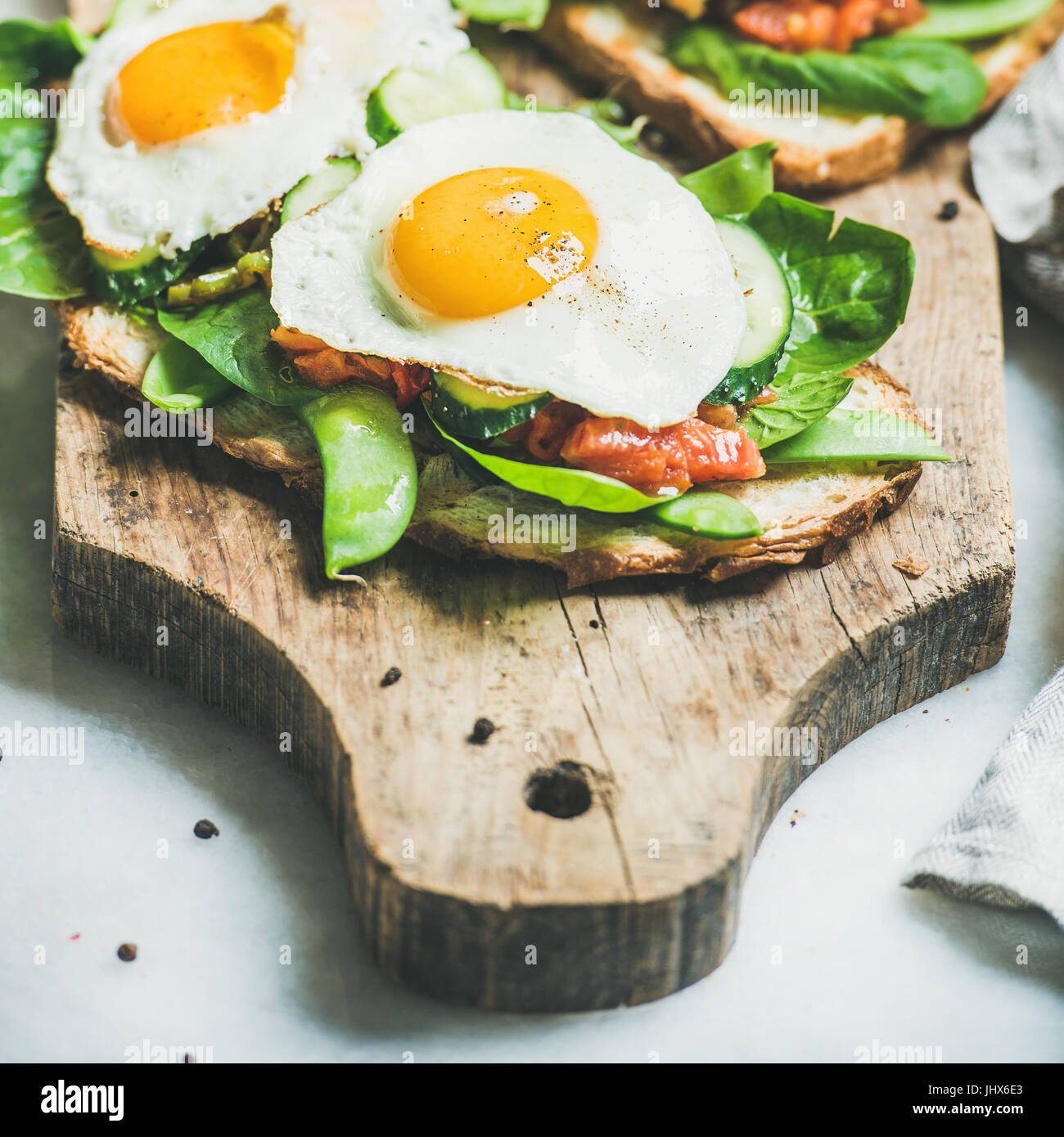 Bread toasts with fried eggs and fresh vegetables, square crop Stock Photo
