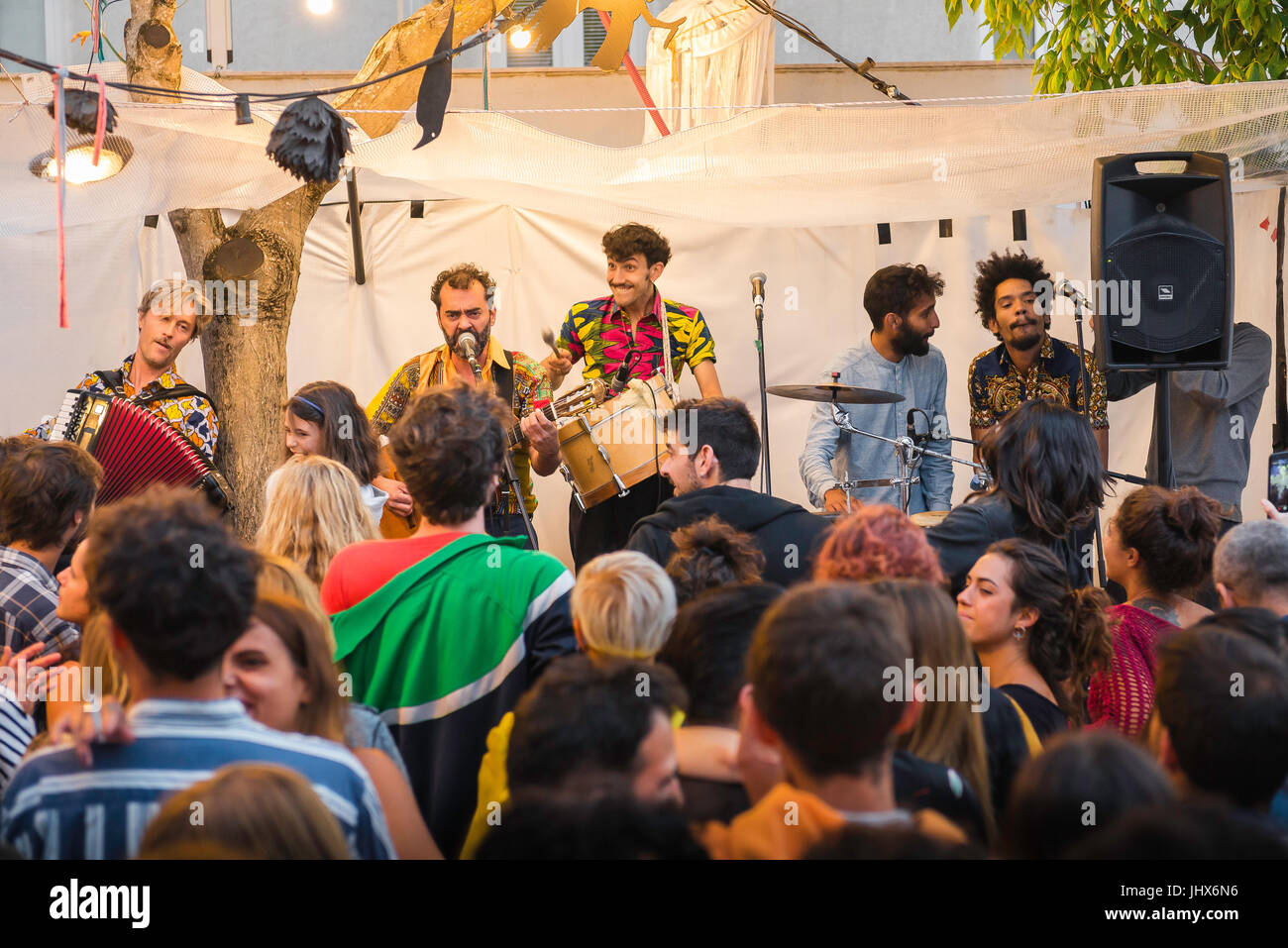 Lisbon nightlife, on a summer evening in the Alfama district a salsa band entertain a lively audience at a busy - Stock Image