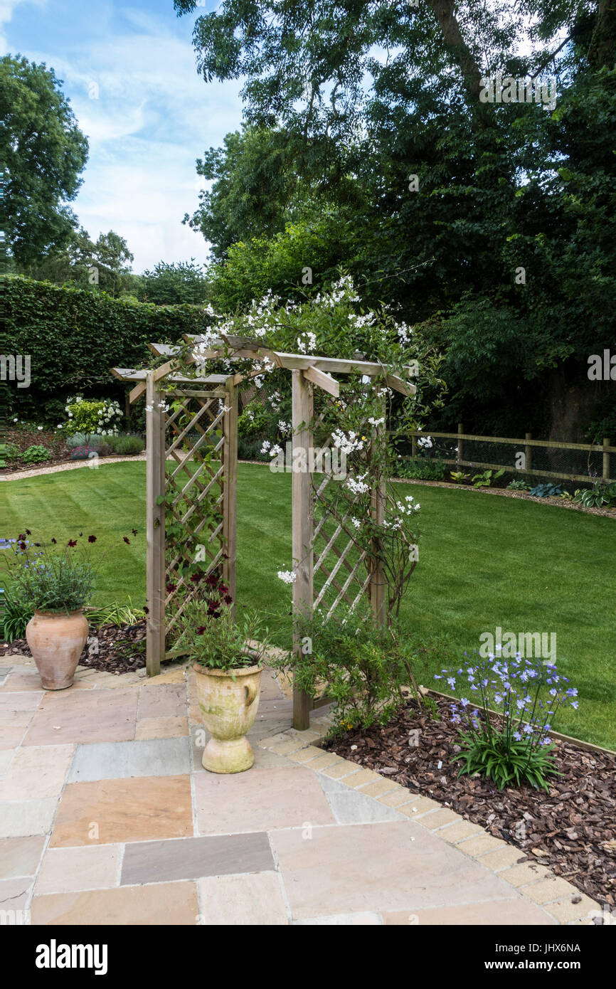 A garden arch covered with jasmine (Jasminum officinale) between a stone patio and lawn, with pots of chocolate - Stock Image