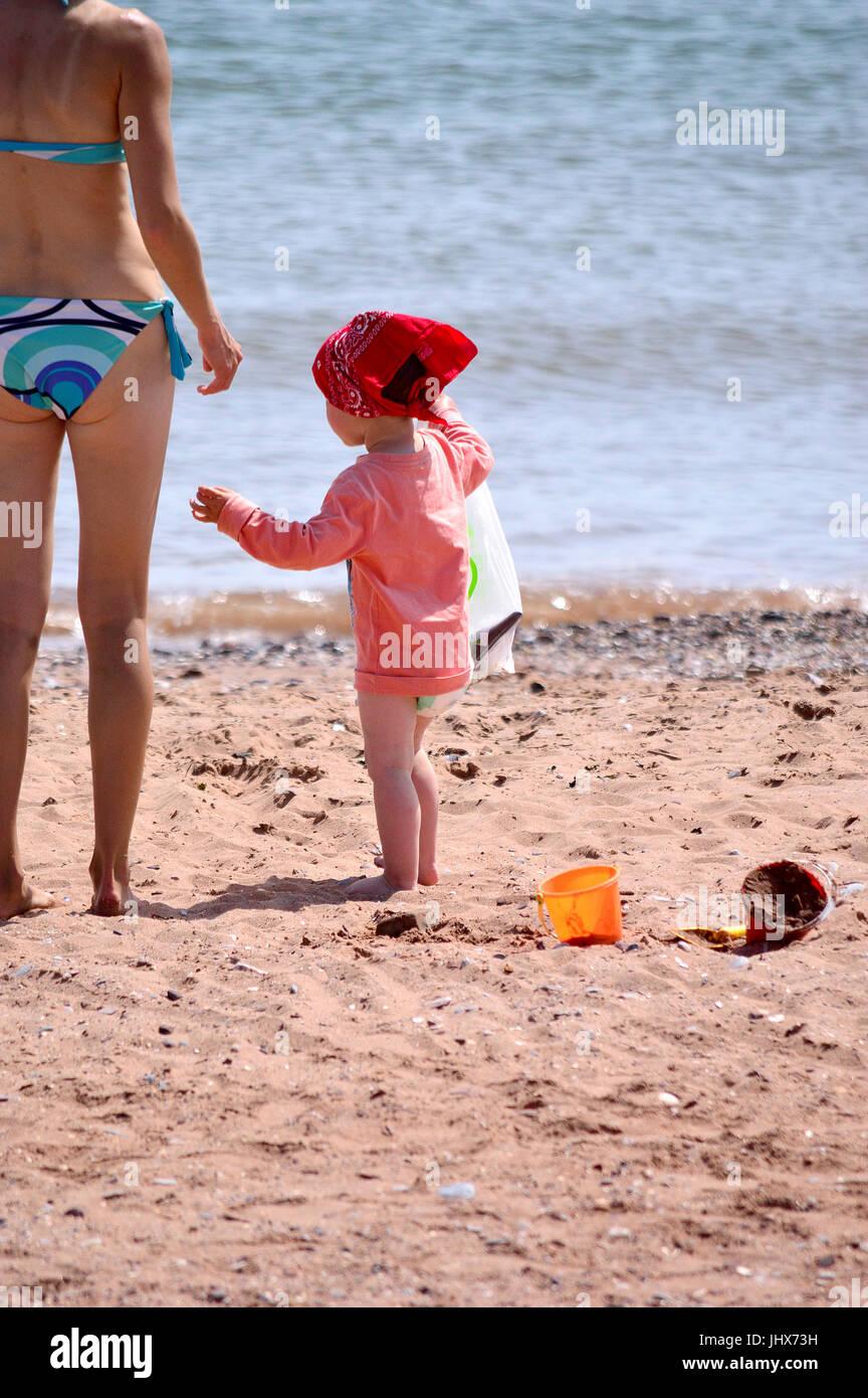 Female in small two-piece bikini, with little girl on beach, a delightful scene - Stock Image