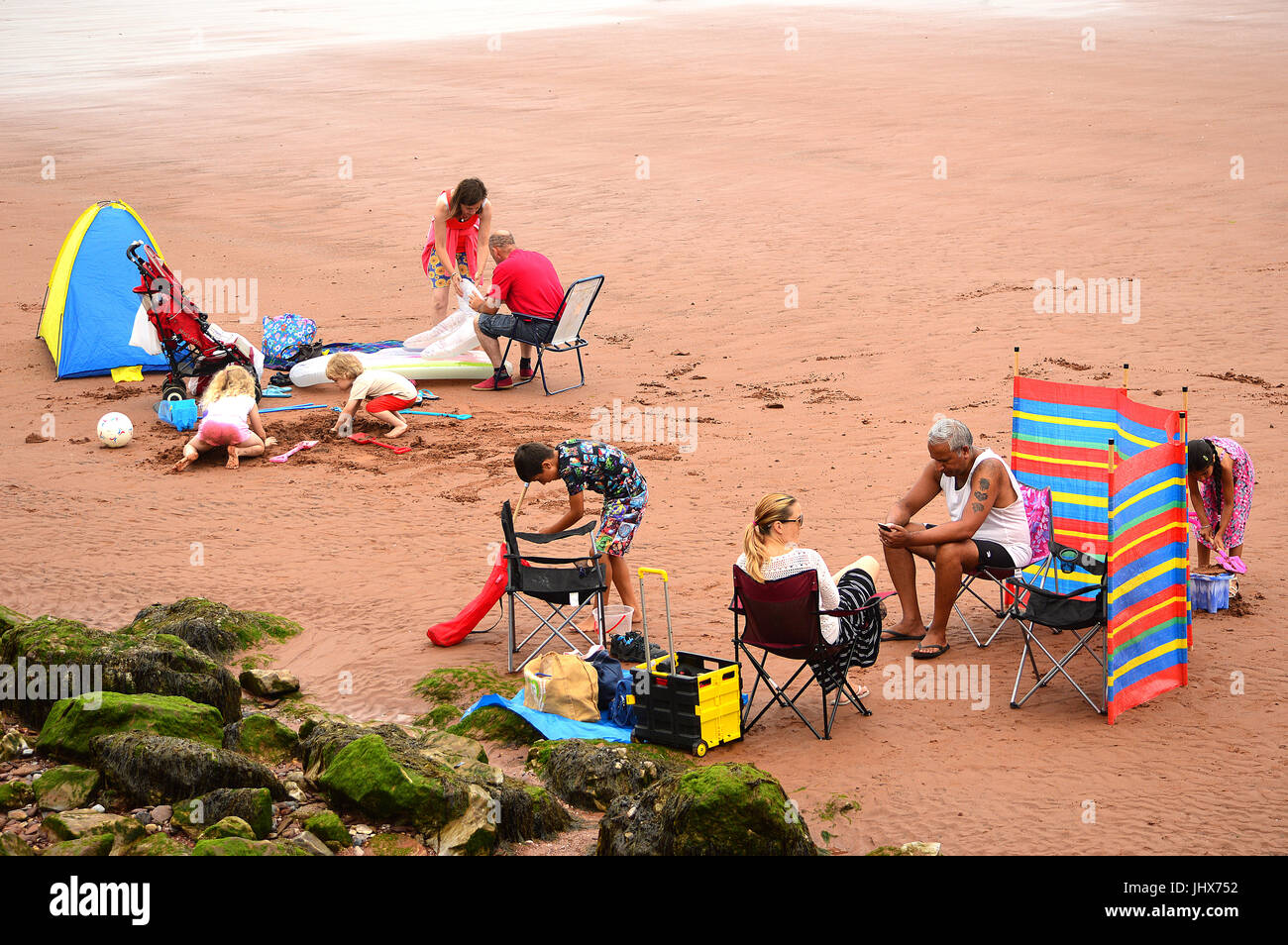 Adults and children all having fun on a sandy seaside beach in Devon - Stock Image