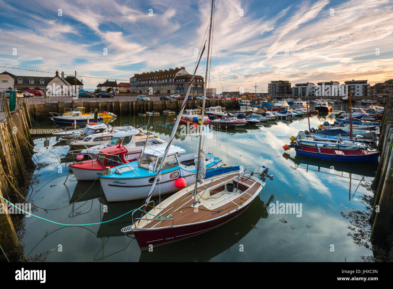 West Bay, Dorset, UK.  16th July 2017.  UK Weather.  A warm settled evening with high wispy cloud above the harbour - Stock Image