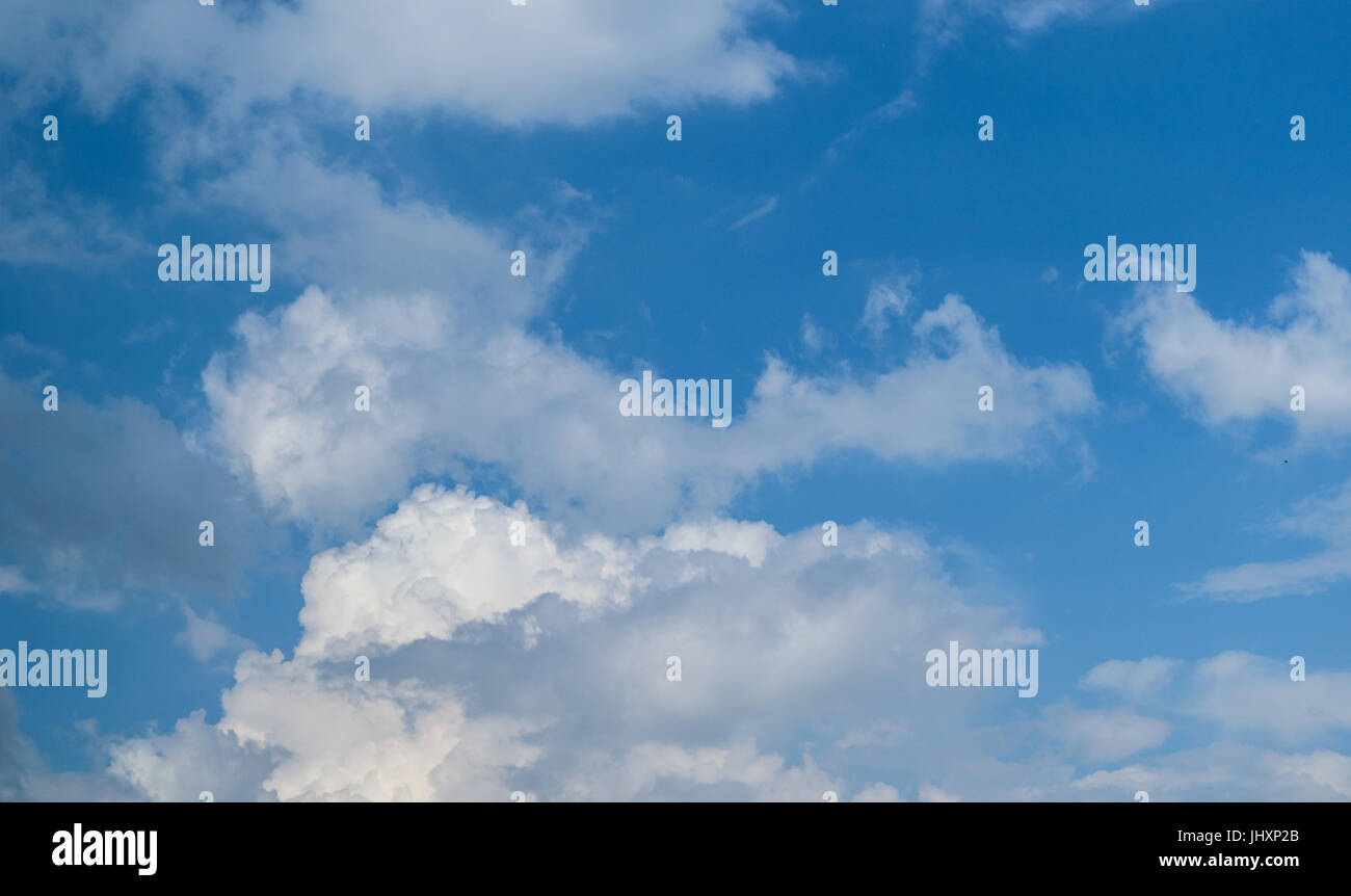 Blue sky with fluffy white clouds. - Stock Image