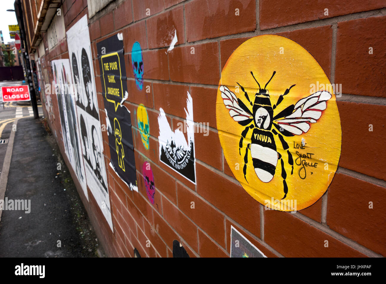 YNWA Manchester Bee on a wall covered with posters on Oldham Street, Northern Quarter, Manchester, UK - Stock Image