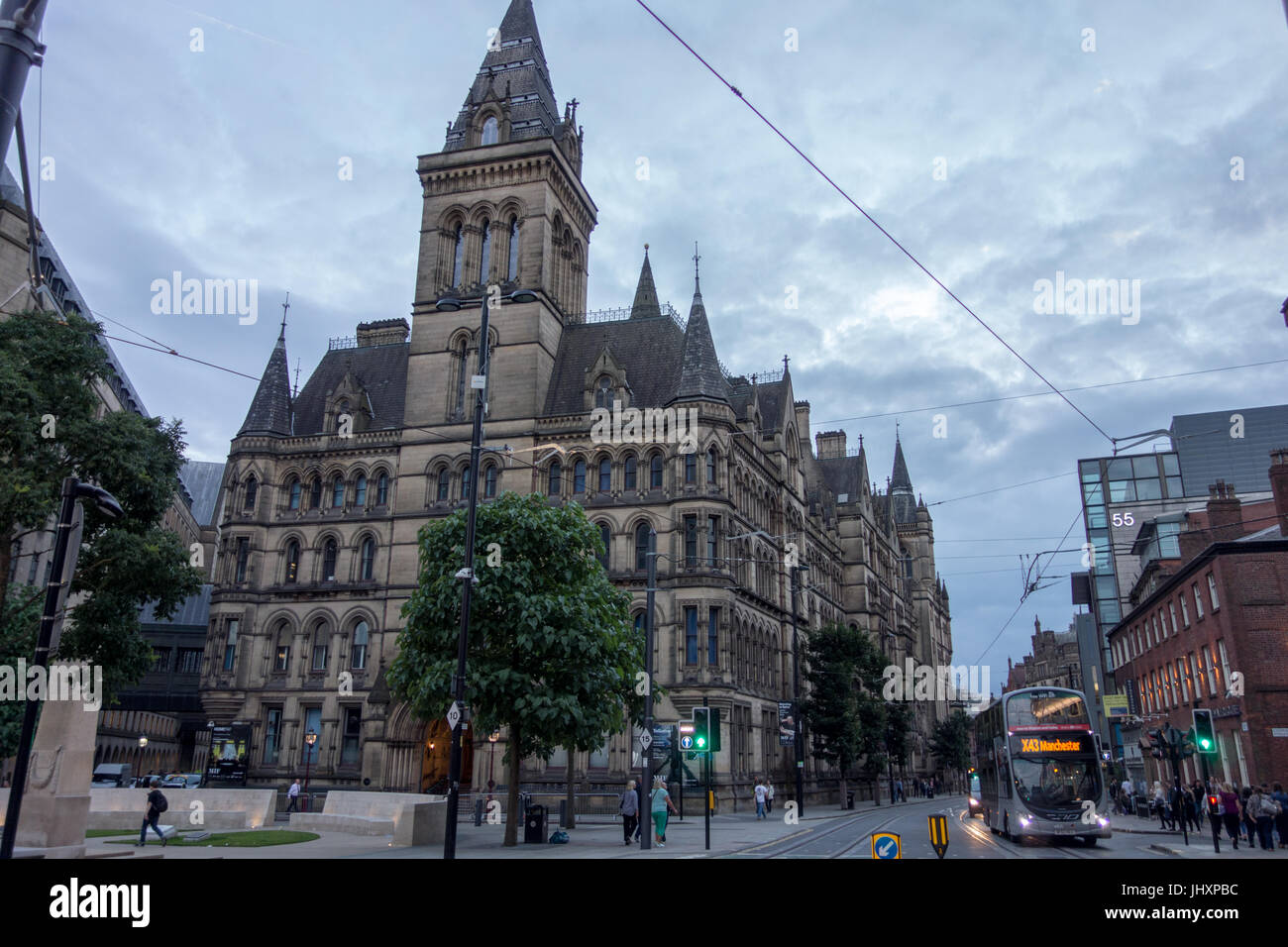 Manchester Town Hall, Manchester, UK - rear view in the evening with an X43 Manchester double decker bus coming - Stock Image