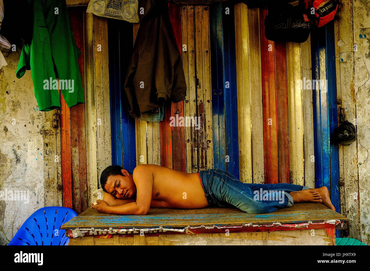An Indonesian man sleeps in the street in Makassar, South Sulawesi, Indonesia - Stock Image