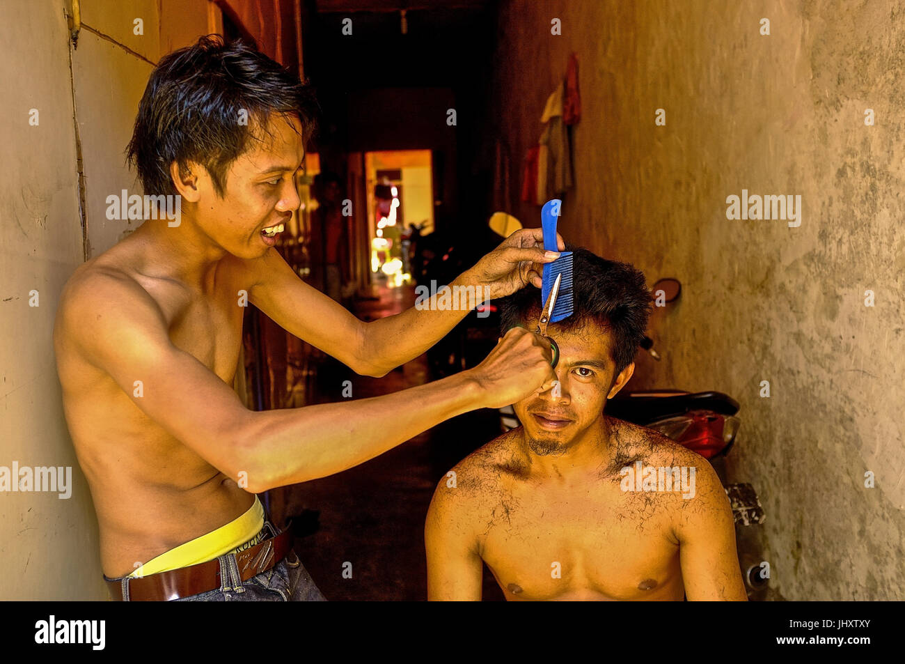A young Indonesian man gets his haircut in Makassar, South Sulawesi, Indonesia - Stock Image