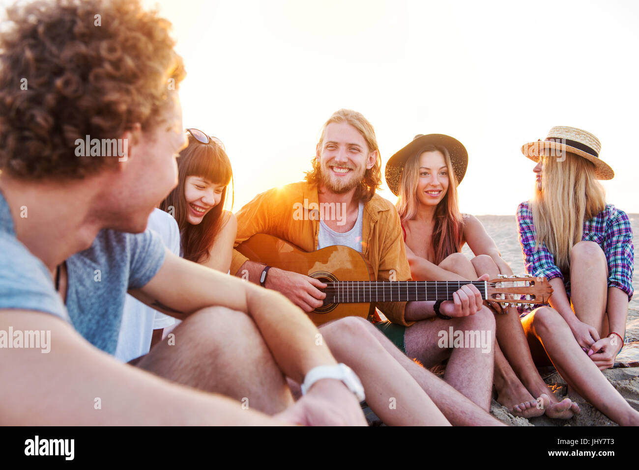 Happy group of friend having party on the beach - Stock Image