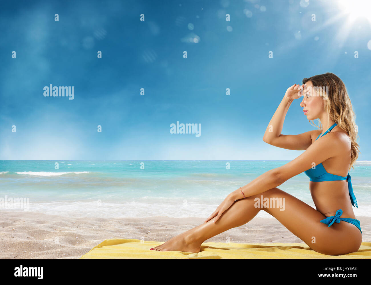 Girl in bikini sits on a beach looking for new travel destination. - Stock Image