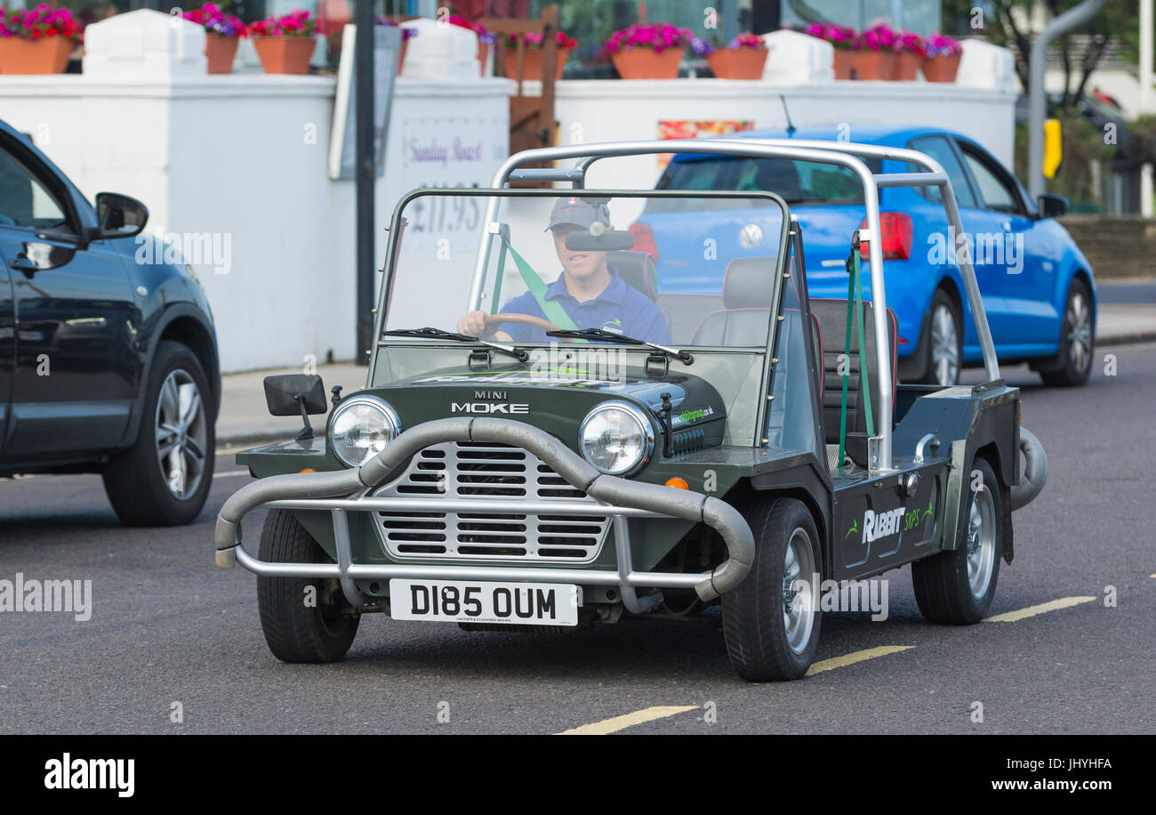 Mini Moke car being driven on a road. - Stock Image