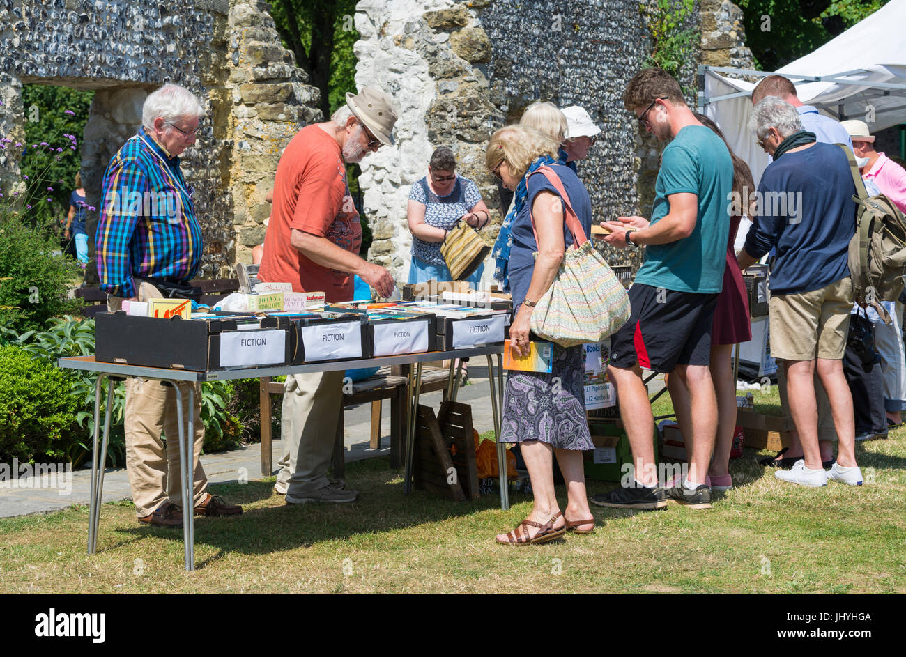 People at a stall selling books at a fete as part of a Summer charity event in the UK. Raising money for charity. - Stock Image