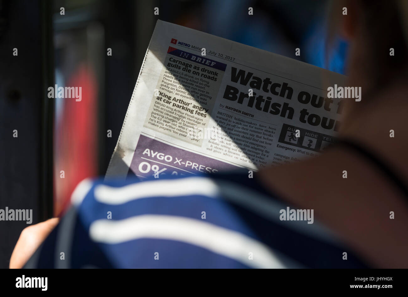 Commuting to work on a bus reading The Metro, a free newspaper in the UK. - Stock Image