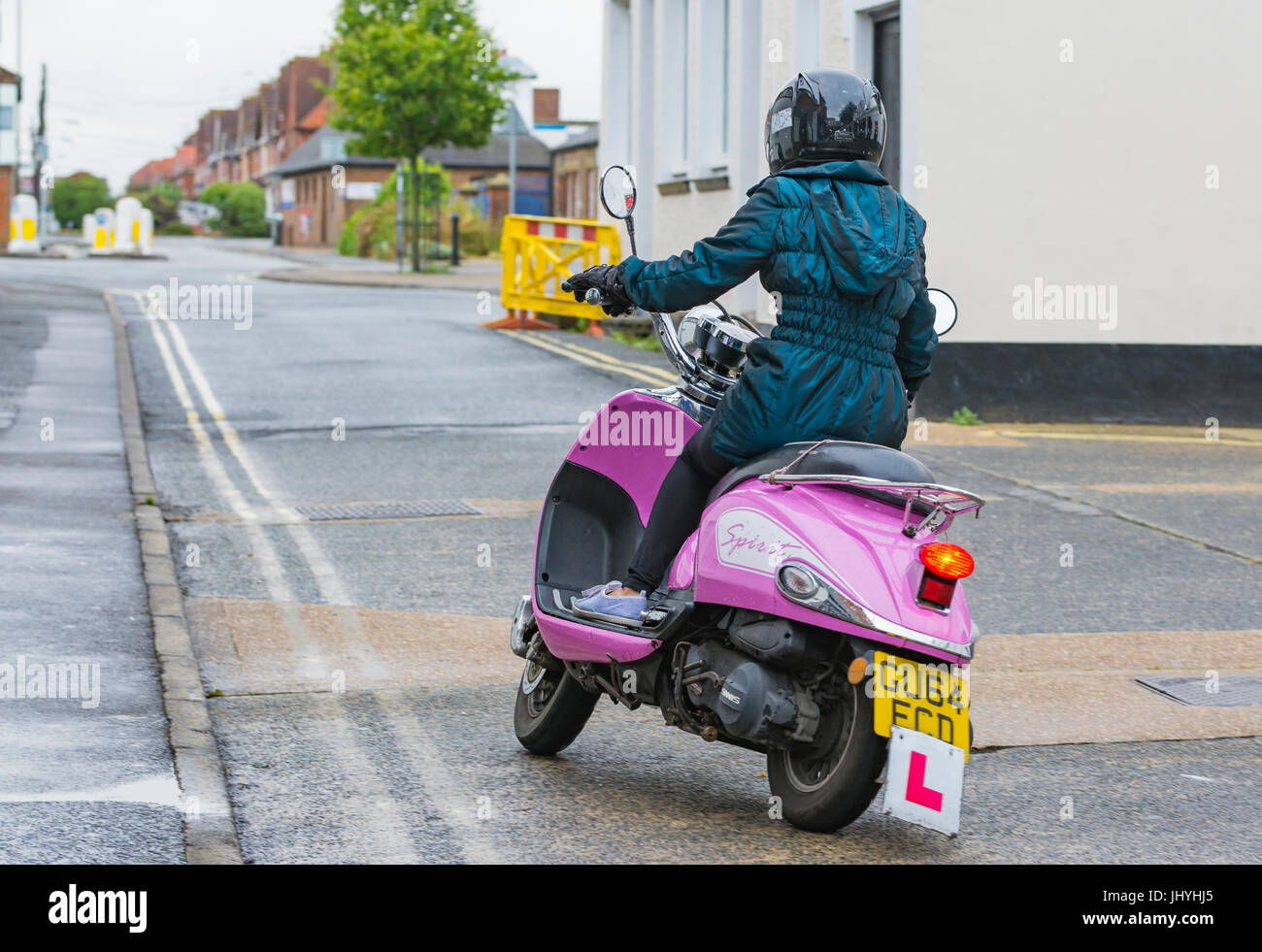 Woman riding a Pink Sinnis Spirit learner retro scooter. - Stock Image