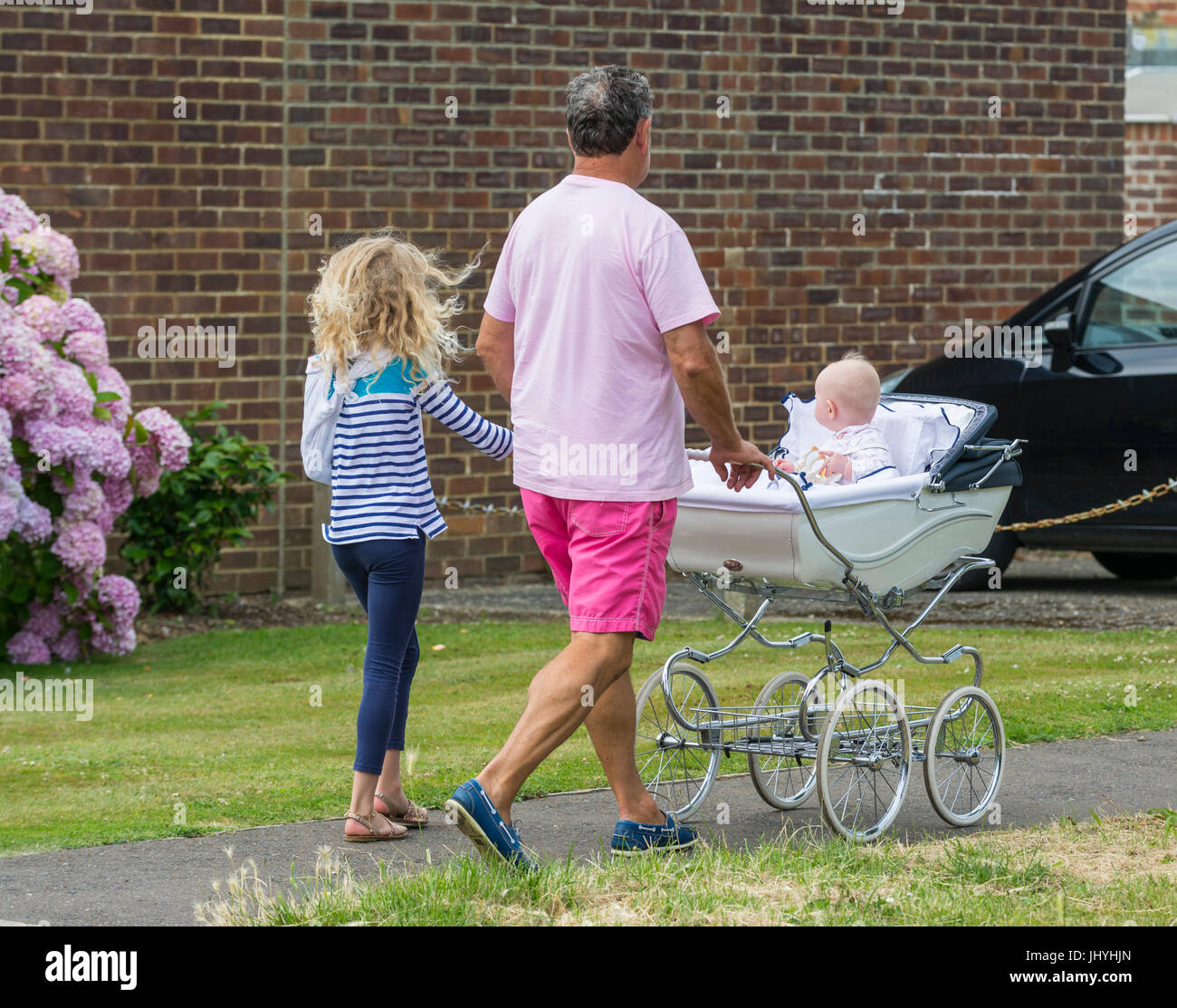 Man walking with a child and pushing a pram with a baby. Single parent family. - Stock Image
