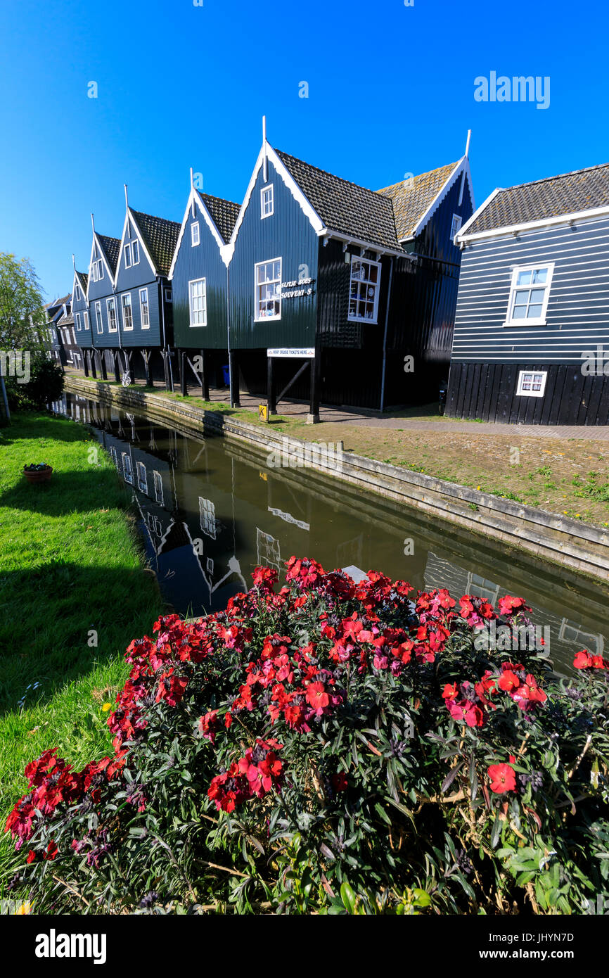 Wooden houses reflected in the canal framed by flowers in the village of Marken, Waterland, North Holland, The Netherlands - Stock Image