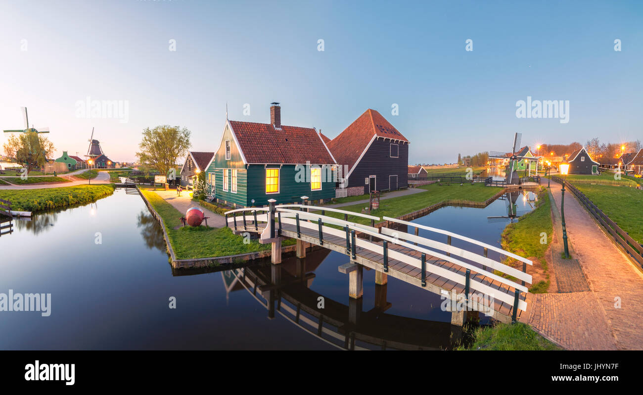 Panorama of wooden houses and windmills of the typical village of Zaanse Schans at dusk, North Holland, The Netherlands, - Stock Image