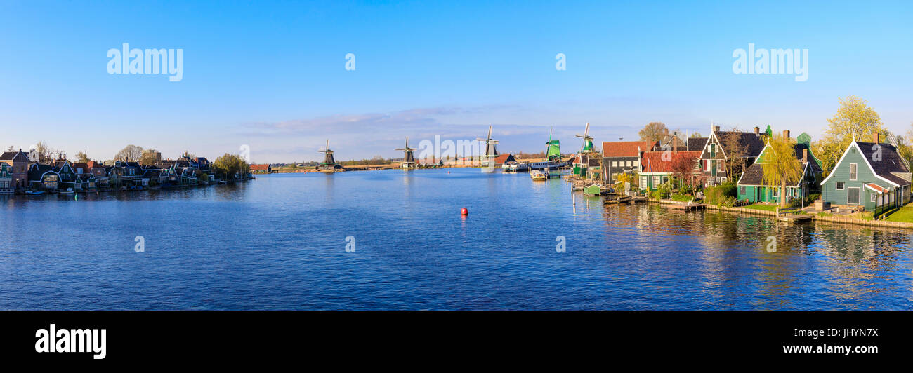 Panorama of wooden houses and windmills framed by the blue River Zaan, Zaanse Schans, North Holland, The Netherlands, - Stock Image
