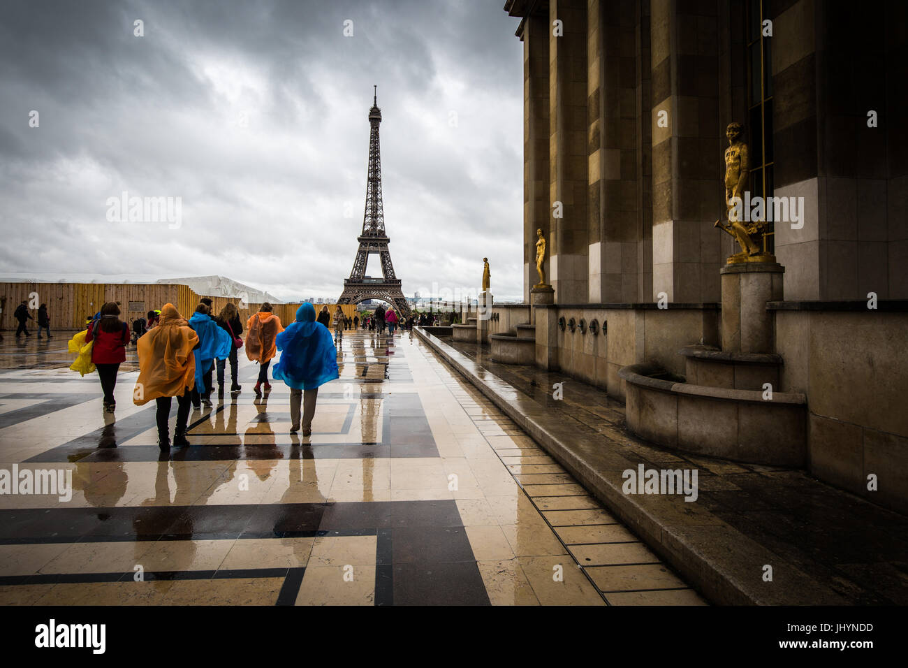 Heading towards the Eiffel Tower, tourists brave the rain in colourful ponchos at the Palais De Chaillot, Paris, - Stock Image
