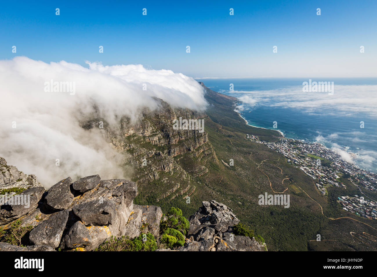 Table Mountain covered in a tablecloth of orographic clouds, Camps Bay below covered in low cloud, Cape Town, South - Stock Image