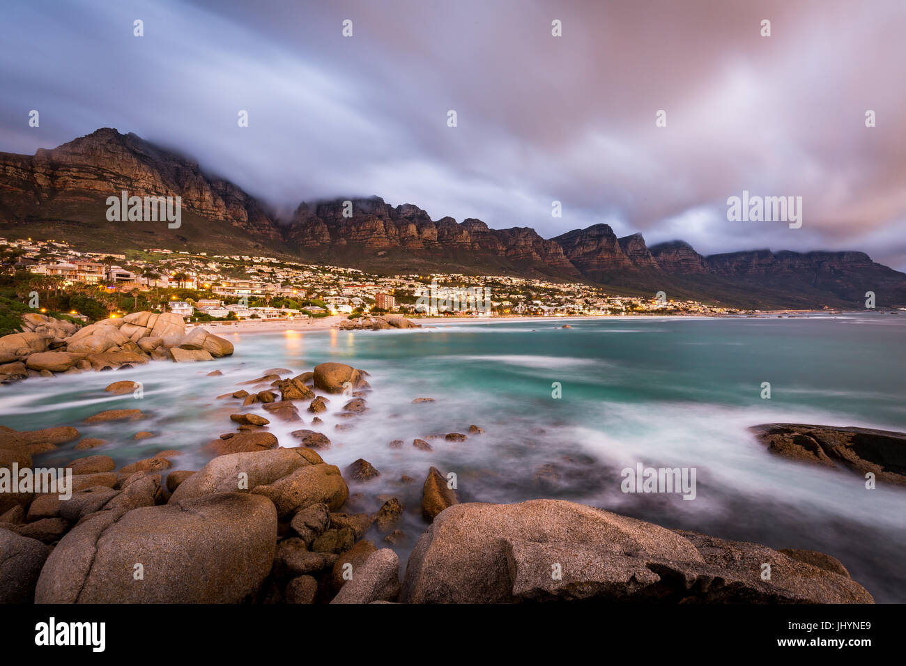 Long exposure at sunset at Camps Bay with cloud over Table Mountain and the Twelve Apostles, Cape Town, South Africa, - Stock Image