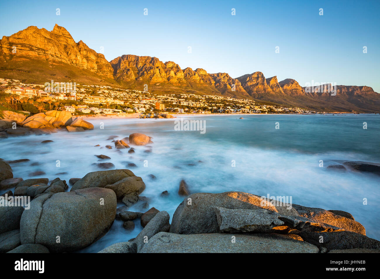 Sunset in Camps Bay with Table Mountain on the left and the Twelve Apostles to the right, Western Cape, South Africa Stock Photo