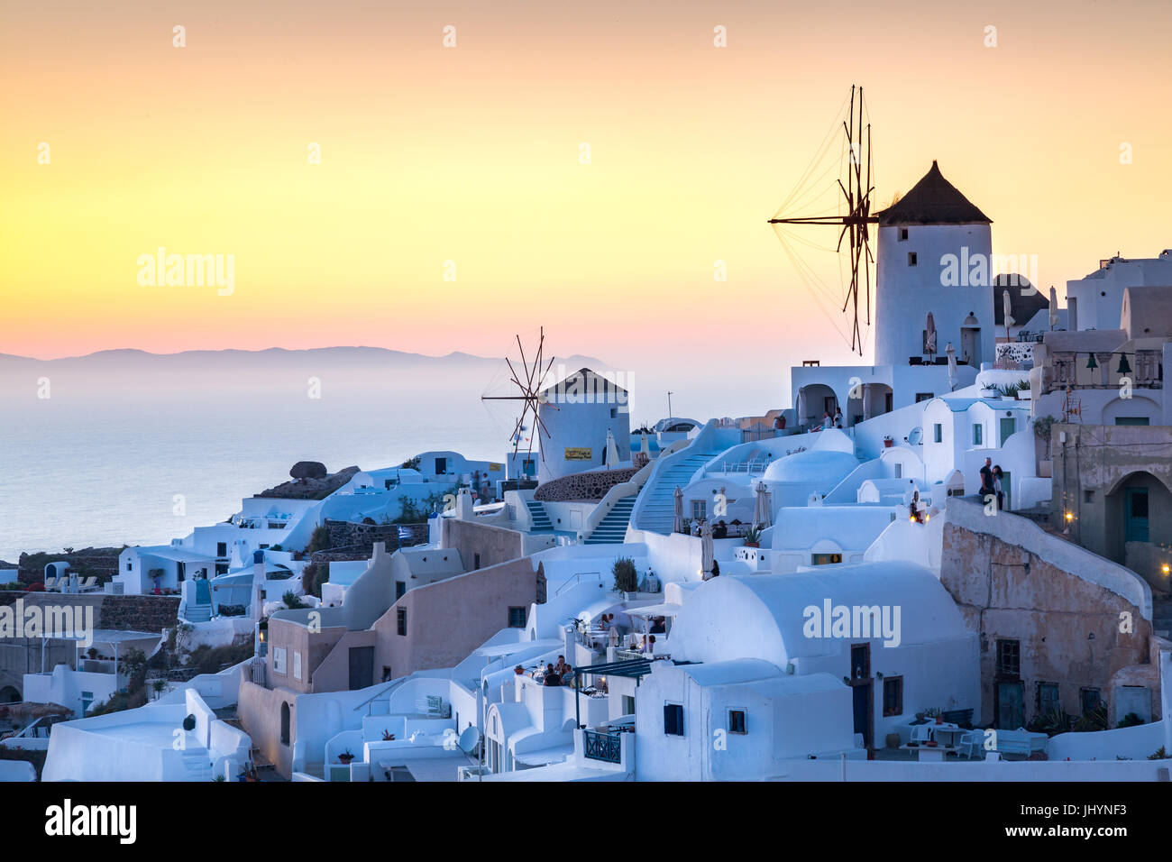 Sunset over the white stone buildings and windmills of Oia on the tip of Santorini's caldera, Santorini, Cyclades, - Stock Image