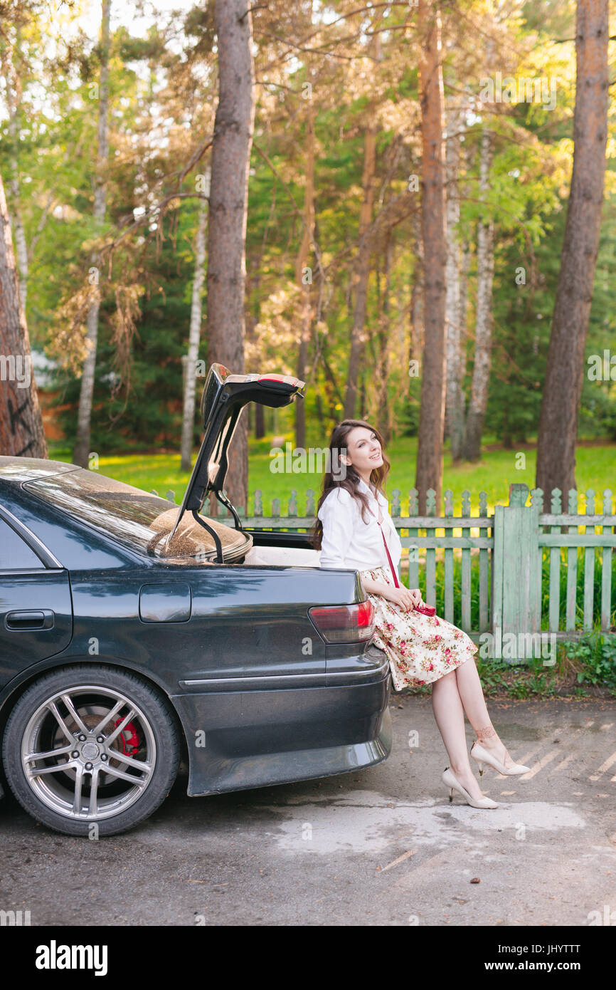 Young woman sitting in the car trunk and using a smart phone on the roadside in the forest - Stock Image