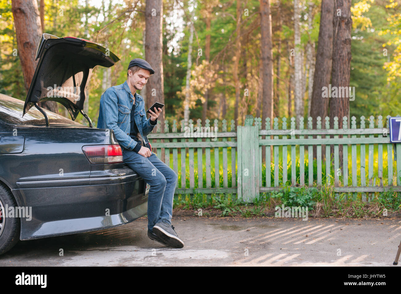 Young man sitting in the car trunk and using a smart phone on the roadside in the forest - Stock Image