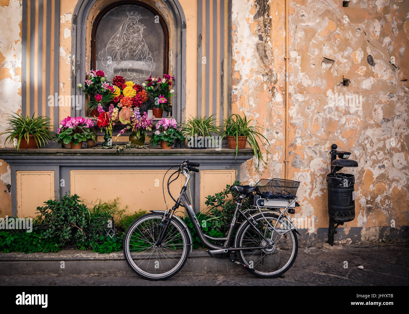 Bike and rustik wall with lot of flowers and Virgin Mary drawing - Stock Image